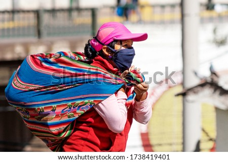 Inka woman in respiratory mask with typical bag on her back sells goods in street during coronavirus pandemic in Latin South America. Epidemic of covid-19