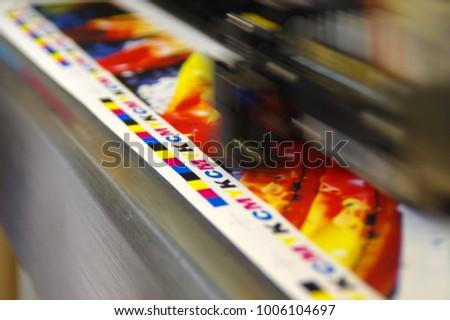 Inkjet plotter printing head moving over CMYK mark on white paper. Large digital printer machine.