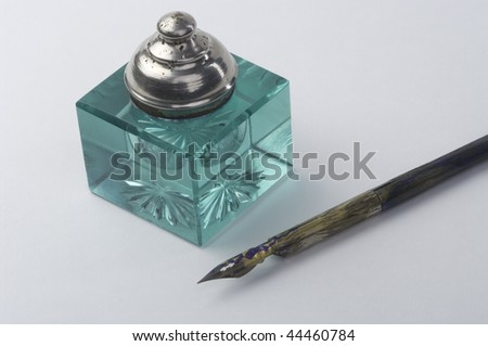 Inkpot with pen on white background