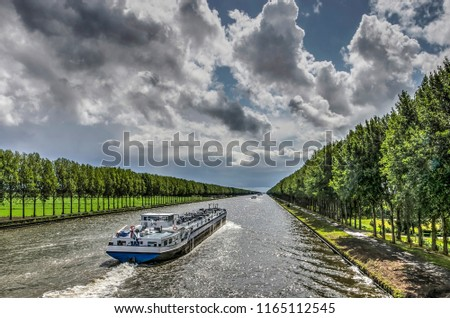Inland barge on the long straight tree-lined Amsterdam-Rhine canal just south of Amsterdam on a day in summer with dramatic cloud formations