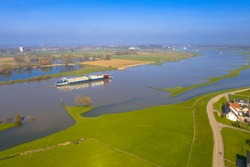 Inland container barge on River Lek aerial view near the village of Ravenswaaij, Gelderland, Netherlands