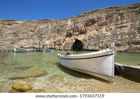 Inland sea tunnel Diversite near former Azure window site on Dwejra at Gozo island in Malta. Empty boats sit in inland sea in front of rock formation separating them from the sea. Foto d'archivio ©