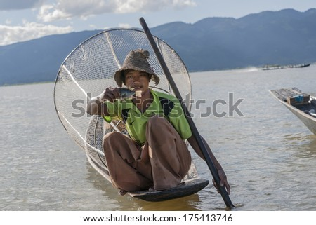 INLE LAKE, MYANMAR - NOVEMBER 3; Burmese fisher proudly holds his small fish to be photographed, squatting on his boat in front of traditional conical fish trap on November 3, 2013. - stock photo