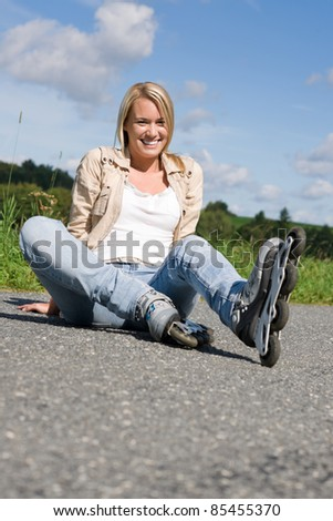 Inline skates young attractive woman wearing jeans sitting asphalt road