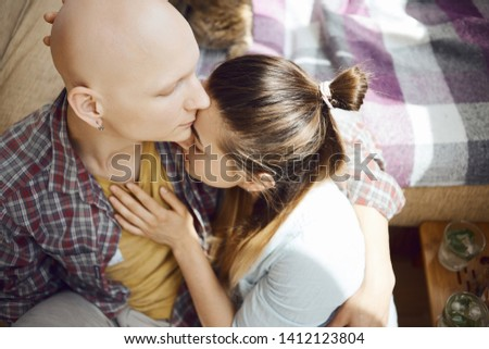 inloved people show tender feelings for each other, woman affectionate touching a man chest by the hand and touches his face by own. young tender enamoured couple spending time together at home #1412123804