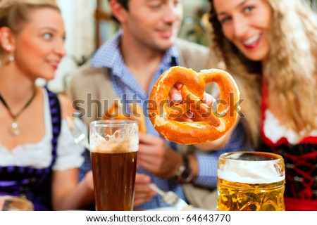 Inn or pub in Bavaria - group of young men and women in traditional Tracht drinking beer and eating pretzel