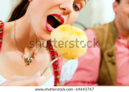 Inn or pub in Bavaria - young woman in Tracht eating dumplings she has put on her fork
