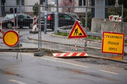 Inner city road closed by signs and boundary around street works. Construction and road work sign in downtown. Caution symbol, work in progress. Translation:''Pedestrians caution!''