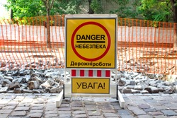 Inner city road with old pavement, closed by stone roadblocks during reconstruction. Yellow roadsign with the words in Ukrainian mean - DANGER, ROAD WORKS, ATTENTION. City street under reconstruction