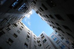 Inner courtyard view from below with clouds - claustrophobia in small building blocks with windows during lockdown