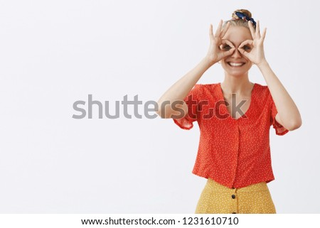 Inner kid wants play. Childish and playful good-looking happy blond female friend in vintage stylish red blouse and skirt, showing zero or okay gesture over eyes as if gazing through binocular or mask
