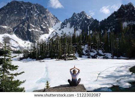 Inner peace and mindfulness. Woman meditating on scenic lakeshore with beautiful view of snow covered mountains. Colchuck Lake. The Enchantments. Leavenworth. Seattle. Washington State. United States