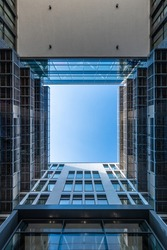 Inner yard of modern office building looking upwards along modern facade into the blue sky