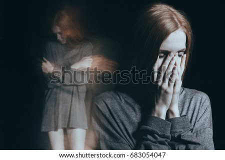 Innocent girl feeling overwhelming loneliness and embraces herself in a mental illness concept