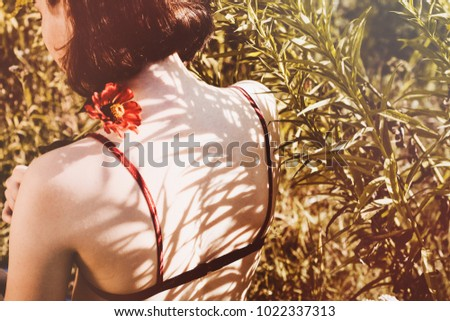 Innocent girl with red flower. Woman in green field. Symbol of innocence, passion. Lingerie, bra. Short hair. Shadow and light. Sunlight and sunny day. Sadness and silence. #1022337313