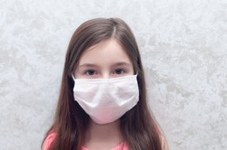 Innocent looking child isolated on background. Caucasian little girl wearing medical face mask. Coronavirus outbreak concept. Concept of quarantine and protecting children from corona virus.