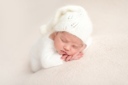 Innocent newborn angel in white knitted suit