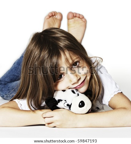 Innocently smiling girl with soft toy lying on floor in studio, isolated on white background.