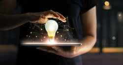 Innovation concept. Hands holding tablet and illuminated light bulb with global network connection on screen, Technology and communication on dark background.
