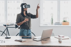 Innovation in business. Confident young woman in virtual reality headset pointing in the air while standing near her working place in office