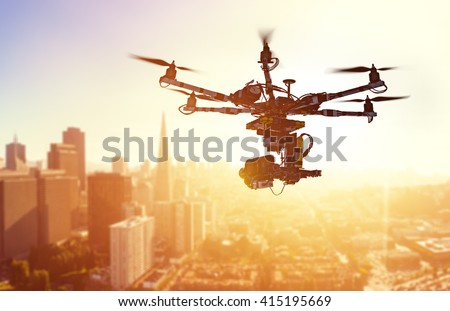 Shutterstock Innovation photography concept. Silhouette drone Flying over San-Francisco city on blurred background. Heavy lift drone photographing city at sunset.