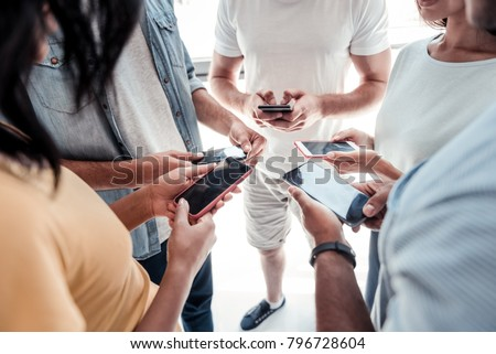 Innovative communication. Scaled up shot of millennial people standing in a circle and working on their smartphones together.