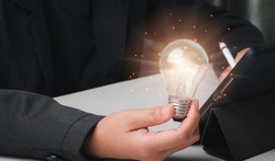Innovative technology and creativity concept. Business man use electronic pen writing on tablet and holding light bulbs or lamp thinking ideas or new ideas and technology digital line.