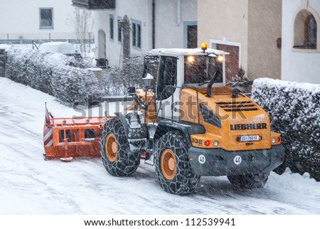 INNSBRUCK; AUSTRIA - JAN 24: Snow removal vehicle removing snow after blizzard which caused several damages on the streets of Innsbruck in Tirol, Austria on January 24, 2012.