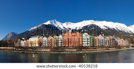 Innsbruck: Panoramic View of Colorful Houses at the Inn Riverside in Innsbruck, Austria. Clear blue sky. Snowy Mountains.