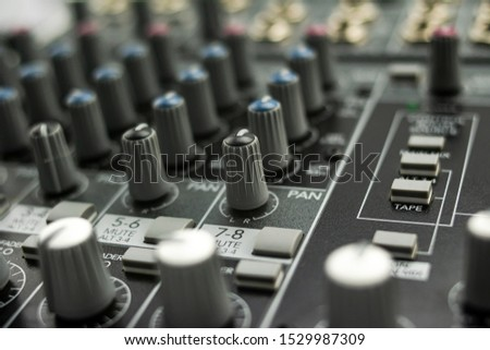 Inputs, equalization and panning on an analog mixing console, with its knobs, keypads and regulators prepared for use it