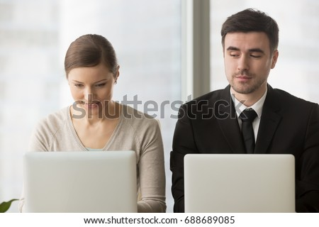 Inquisitive curious businessman with bad manners sneakly looking at laptop screen of businesswoman trying to steal idea of competitor, copying work at corporate exam, gathering information on rival - Shutterstock ID 688689085