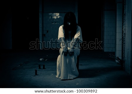 Insane woman sitting on chair in  a white dress