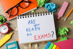 Inscription Are you ready for exams? and different stationary on wooden background, top view