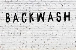 Inscription backwash written with black paint on white brick wall.
