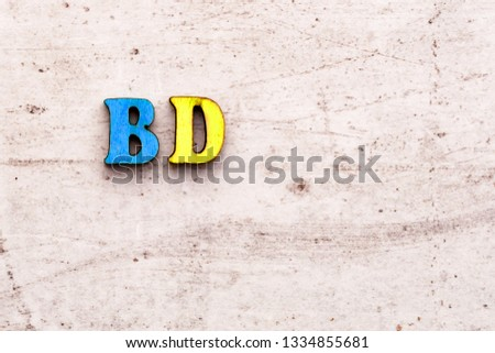 Inscription BD BDAY birthday COLORED abbreviation in wooden letters on a light background.