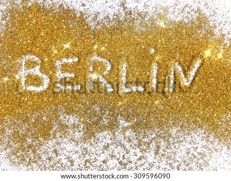 Inscription Berlin on golden glitter sparkles on white background