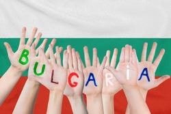 Inscription Bulgaria on the children's hands against the background of a waving flag of the Bulgaria