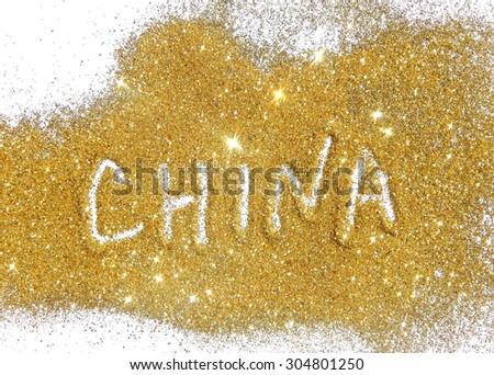 Inscription China on golden glitter sparkles on white background