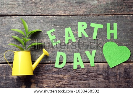 Inscription Earth Day with young plant in watering can on grey wooden table