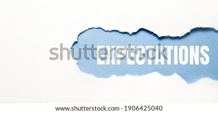 inscription Expectations word on blue torn papper. Foto stock ©