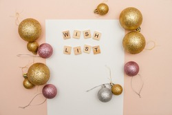 Inscription from wooden blocks wish list on a white blank sheet of paper. New Year's wish list.