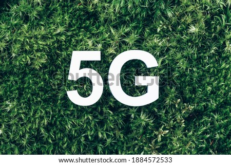 Inscription 5G on moss, green grass background. Top view. Banner. Biophilia concept. Network Internet, mobile wireless business concept. 5G standard of signal transmission technology. stock photo