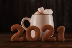 Inscription 2021 gingerbread cookie. Happy new year 2021 and marshmallows in a mug on a dark background close up and copy space. Marshmallow in a cup with gingerbread cookie pattern top view in a dark
