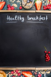 Inscription Healthy Breakfast on blank black chalkboard background. Healthy Breakfast with berries, muesli and nuts, frame. Healthy food and Clean Eating concept