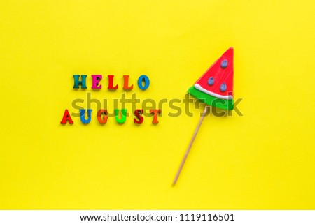 inscription hello august and watermelon lollipop. Still life on yellow background. Copy space, Flat lay, Top view, greeting card. Concept summer and vacation