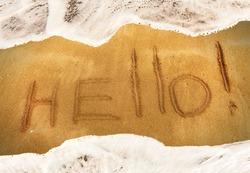 inscription HELLO on the black sand