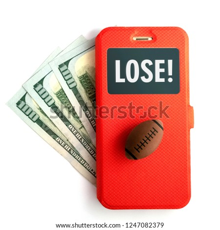 Inscription LOSE on the smartphone screen. The concept of losing sports betting. A ball for American football or rugby and a mobile phone in a red case lies on three hundred US dollars on a white