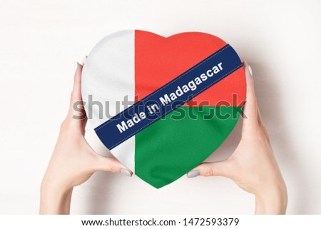 Inscription Made in Madagascar, the flag of Madagascar. Female hands holding a heart shaped box. White background.
