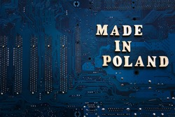 Inscription Made in Poland on a blue electronic printed circuit board. Background with copyspace for design. Polish electronics manufacturing concept.