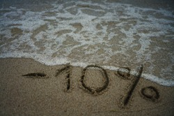 inscription minus ten percent on the sand near the ocean. Discount on vacation at the sea. -10%. inscription on the sand minus 10 percent